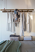 Old ladder suspended and used as clothes rack in bedroom