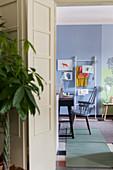 Blick durch Falttür in blau-grünen Wohnraum mit Schreibtisch und Leiterregal für Magazine