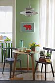 Kleiner runder Tisch mit Holzstühlen als platzsparender Essplatz neben Kücheneingang