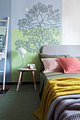 Bed and side table against wall with hand-painted tree mural