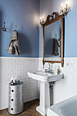 Wooden-framed mirror and old-fashioned wall lamps above vintage-style sink
