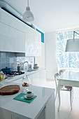 White fitted kitchen with counter, table and chairs