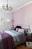 Double bed against pink bedroom wall