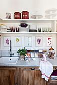 Bilder und offenes Regal über Küchenunterschrank mit Gewürzdosen