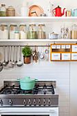 Gas cooker below storage jars on shelves in kitchen