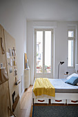 Bed with drawers and wall-mounted organiser in bedroom of period apartment