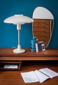 Table lamp and retro mirror on dark wooden desk