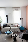 Scatter cushions on loose-covered sofa below window and side tables on round rug