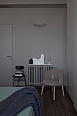 Upholstered chair in front of radiator in bedroom