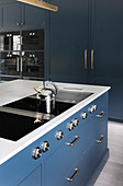 Modern hob on island counter in classic, blue-grey kitchen