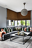 Colourful scatter cushions on grey velvet sofa in front of corner windows with fabric blinds