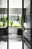Many houseplants in bathroom seen through open, sliding glass doors