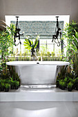 Fabric monkeys above free-standing bathtub and plants on platform