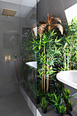 Golden palm tree, bamboo and artificial plants in luxury bathroom