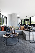 Round coffee table in front of sofa in open-plan living room in shades of grey