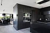 Black, modern kitchen in open-plan interior in shades of grey