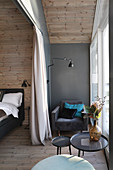 Armchair next to window in elegant bedroom with wood-clad walls