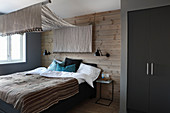 Bedroom in earthy shades with canopy over bed and wood-clad walls