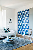 Decorative blue-and-white geometric pattern behind sliding wall in living area