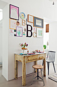 Alter schmaler Holztisch unter Bildergalerie als Frühstückstisch für Zwei