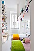 Lichtdurchfluteter Schlafbereich für Kinder mit Betten und deckenhohem Wandregal mit Schreibtisch