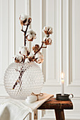 Wintry arrangement of cotton bolls in glass vase