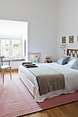 White walls, double bed and pink rug in bright, feminine bedroom