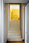 Schlichter weißer Treppenaufgang zu Wohnraum mit sonnengelben Wänden