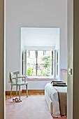 Pink rug and window seat in bright, feminine bedroom