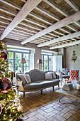 Wohnzimmer mit Tannenbaum und grauem Polstersofa in renoviertem Bauernhaus