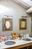 Marble washstand and gilt-framed mirrors in festively decorated bathroom
