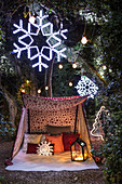 Cushions and lanterns in tent in garden decorated with snowflakes and fairy lights