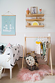 Clothes rail in contemporary child's bedroom in pastel shades