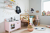 Pink play kitchen next to cot in girl's bedroom in pastel shades