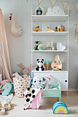 Cute children's accessories on shelves in girl's bedroom in pastel shades