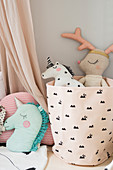 Soft toys in pink fabric storage basket