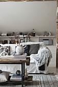 Gemütliche Sitzecke mit Sofa und rustikalem Holz-Couchtisch in Dachzimmer