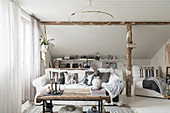 Comfortable sofa and chaise chair in attic room with wooden beams