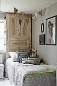 Bohemian-style child's bedroom with old door used as bed headboard