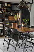 Dining table and black folding chairs in front of rusty metal shelves