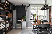 Dining table and folding chairs, large chalkboard and rusty metal shelving