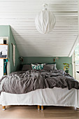 Bett unter der Schräge mit grünem Kniestock und Deckenverkleidung