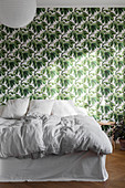 White bed with valance against leaf-patterned wallpaper in bedroom