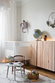 Floating wooden cabinet and cot in simple nursery