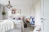 Elegantes Schlafzimmer in Weiß mit Boxspringbett und Kronleuchter