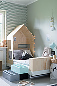 Steps made from oversize Lego bricks leading to bed with house-shaped canopy in child's bedroom
