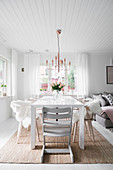 Grey high chair at dining table in bright, open-plan interior