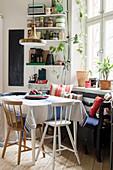 Highchair and bench around kitchen table below window