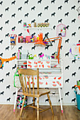 Golden chair at old desk in child's bedroom with horse-patterned wallpaper