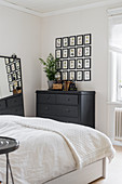 Pictures of birds arranged in a square above chest of drawers in bedroom